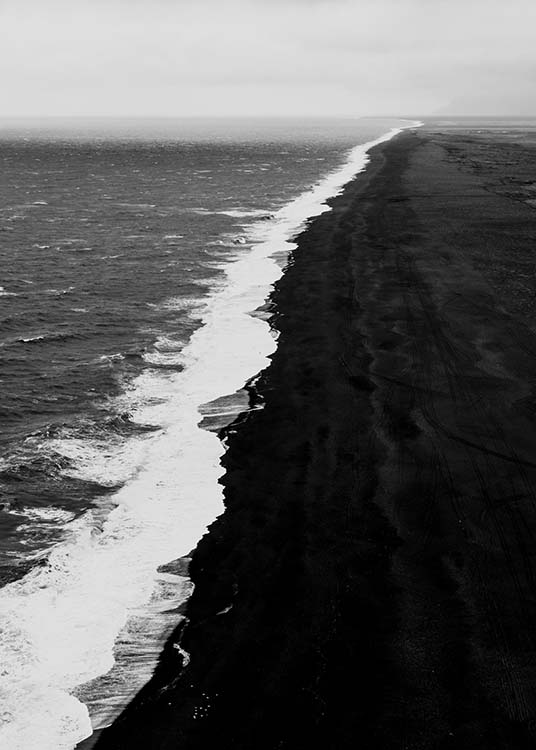 - Black and white aerial shot of the coast with a black beach and powerful waves.