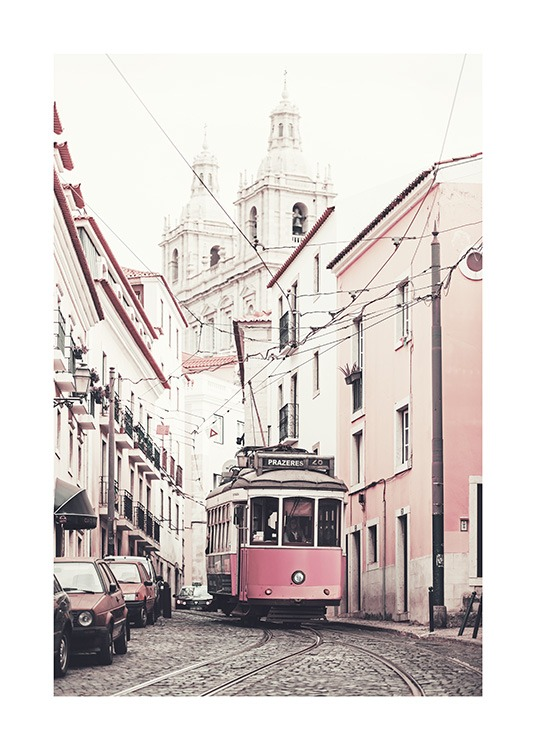 – Photograph of pink and white buildings on the side of a road with a tram in the middle