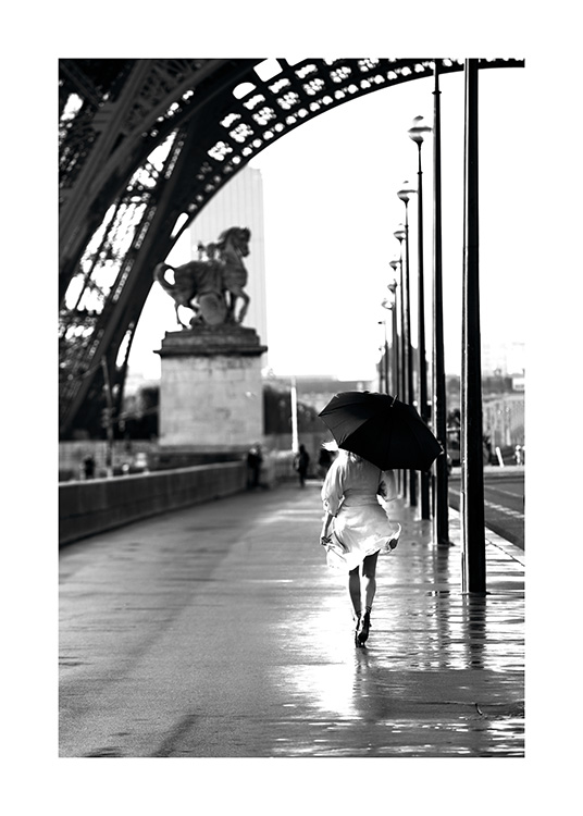 – Black and white photograph of a woman walking with an umbrella underneath the Eiffel Tower