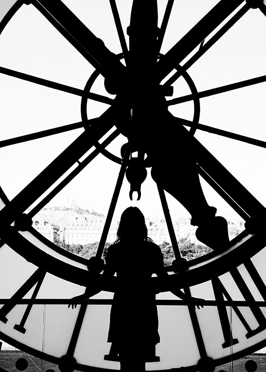 - Black and white photo poster of a woman in front of a large church clock in Paris.