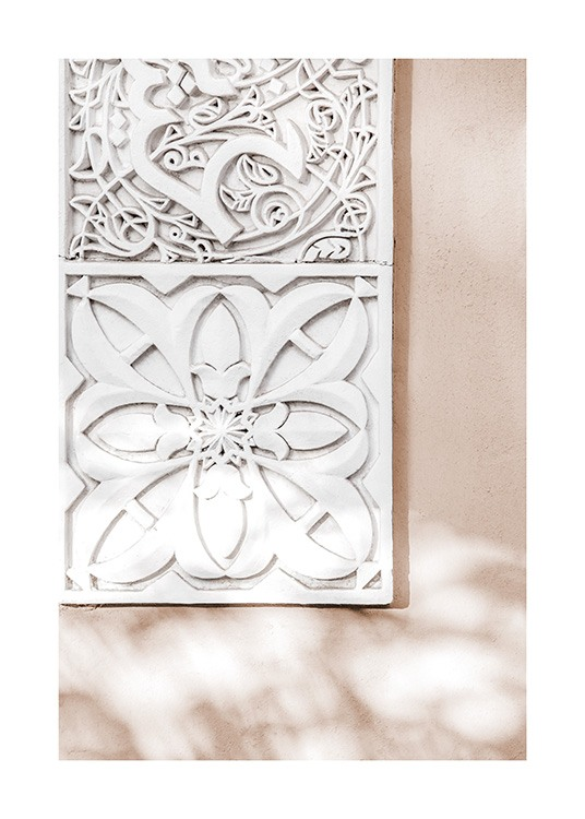 - Photograph of carved tiles in white against a light pink background