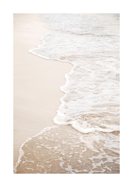 – Photograph of a beach with still waves coming onto the sand