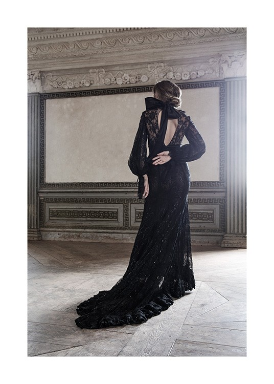 – Photograph of a woman in a black, lace gown with a bow at the neck, standing in a baroque room