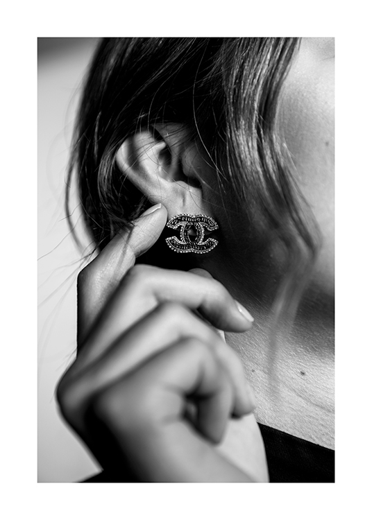 – Black and white photograph of a woman with a Chanel earring lightly touching her ear