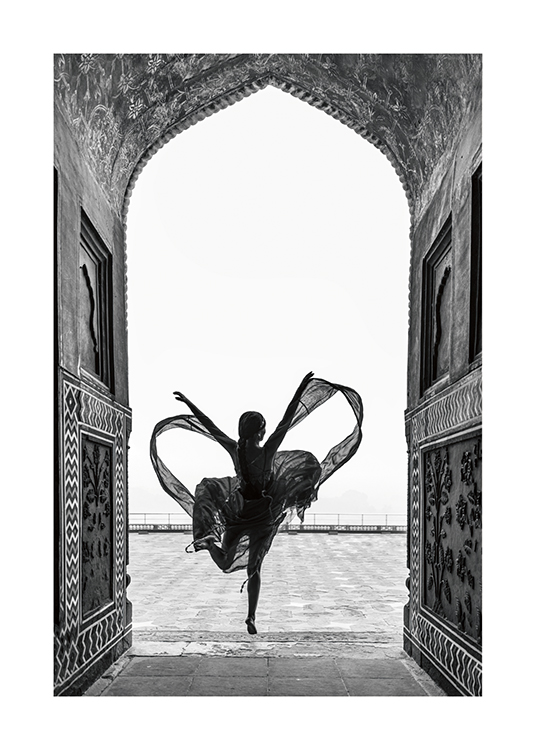 – Black and white photograph of a woman dancing on one leg in a flowy dress, framed by an arch
