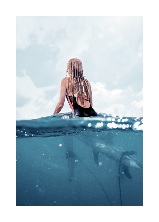 – Photograph of a woman sitting on a surfboard in the ocean, seen from behind