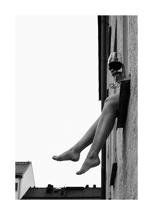 – Black and white photograph of a pair of legs and hand holding a glass of wine sticking out of a window