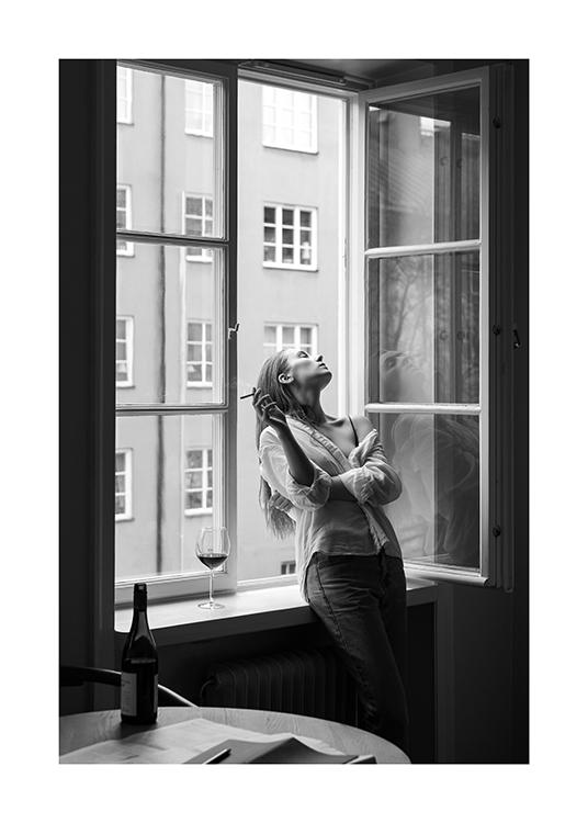– Black and white photograph of a woman holding a cigarette, leaning back in an open window