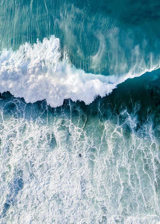– Photograph from above of an ocean with large wave coming towards a surfer