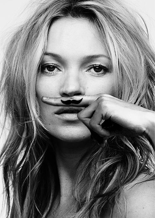 – Black and white photograph of Kate Moss with a finger above her mouth with a moustache on the finger